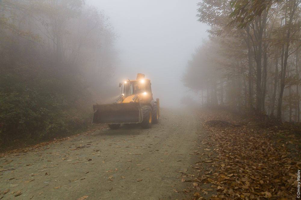 Трактор едет в тумане по грунтовке на Святой Горе Афон