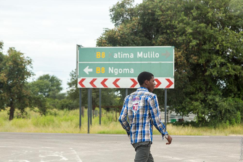 Ngoma - Katima Mulilo road sign in Bukalo and a local guy, Caprivi strip, Namibia, Africa. Местный житель-парень и дорожный знак Нгома - Катима-Мулило в Букало, Намибия, Африка