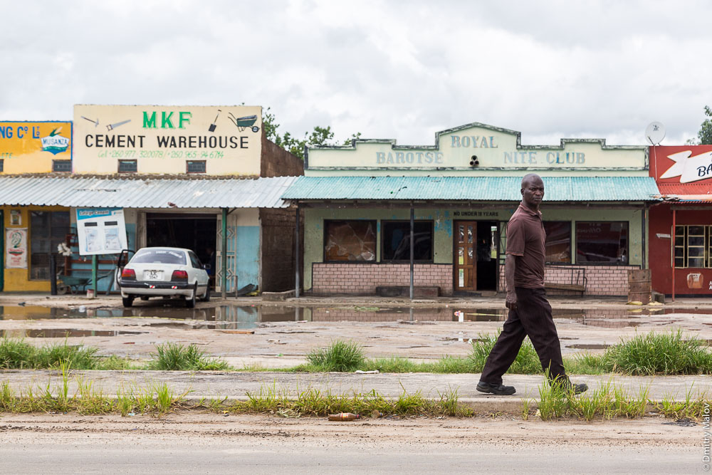 Black man on streets of Sesheke town, Zambia, Africa. Чёрный африканец на улице города Сешеке, Замбия, Африка. MKF Cement Warehouse. Barotse Royal Nite Club.
