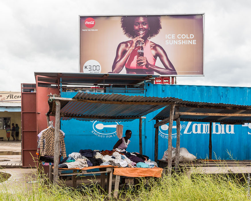Zambia, Sesheke, Africa, billboard, advertisement, Coca-Cola, taste the feeling, ice cold sunshine, energy for life, beautiful young black lady. Замбия, город Шешеке, Африка, суперком, брэндмауэр, реклама, прекрасная чёрная девушка, негритянки, кока-кола