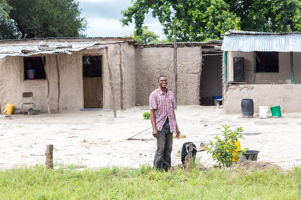 A black lozi man. Lozi house by M10 road Zambia, Sesheke town - Livingstone, Barotseland, Africa. Трасса Сешеке-Ливингстон, Замбия, Баротселенд, Африка. Дом народа лози. Черный африканец племени лози.
