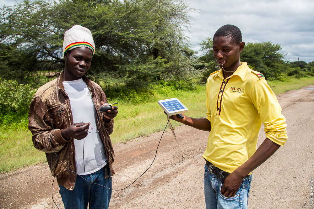 Two young black african lozi guys use solar panel to charge Nokia cell phone BL-4C battery, M10 road Zambia, Sesheke town - Livingstone, Barotseland, Africa. Трасса Сешеке-Ливингстон, Замбия, Баротселенд, Африка. Два чёрных африканца племени лози заряжают батарею BL-4C Nokia от солнеченой панели