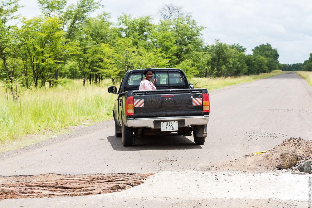 Black african lozi lady on pickup truck AIB 1016 on M10 road Zambia, Barotseland, Sesheke town - Livingstone, Africa. Трасса Сешеке-Ливингстон, Баротселенд, Замбия, Африка, черная женщина лози едет в кузове пикапа