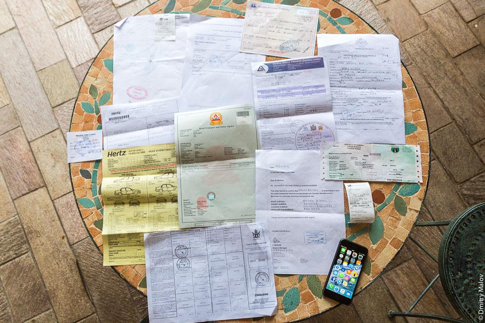 Коллекция полицейских, таможенных и пограничных бумаг и разрешений для поездки вокруг водопада Виктория по маршруту Зимбабве—Ботсвана—Намибия—Замбия на арендованной машине. Papers to go around Victoria falls via Zimbabwe-Botswana-Namibia-Zambia route on a rental car