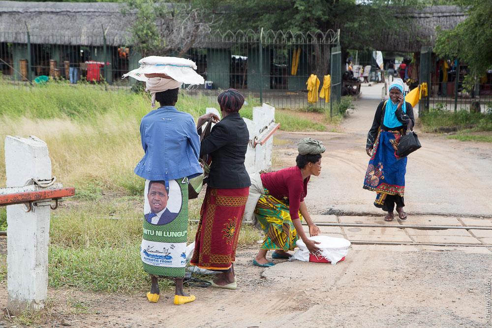 African women carry loads on their heads near Zambia-Zimbabwe border on Zimbabwean side of Victoria Falls. Umuntu ni Lungu skirt. Африканские женщины с грузом на голове, около водопада Виктория, Зимбабвийская сторона