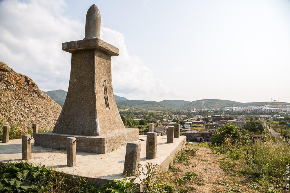Стела сэнсоокинэнхи, часть храма Томариору-дзиндзя на фоне города Томари, Сахалин. Japanese war memorial stela Sensokinenhi in form of shell, part of Tomarioru-jinja Shrine, the town of Tomari, Sakhalin