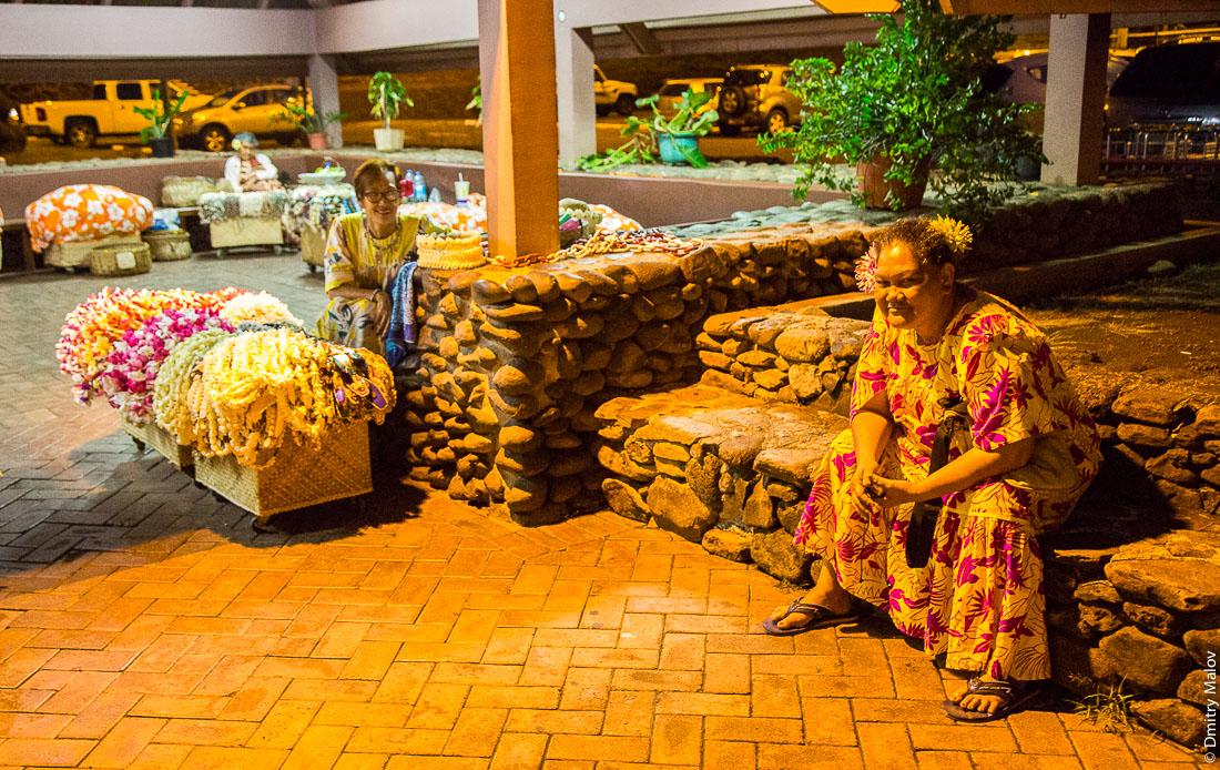 Таитянки готовятся к встрече пассажиров ночного рейса на Таити с гирляндами цветов, аэропорт Фааа, Французская Полинезия. Tahitian women waiting to greet guest from a night flight to Tahiti with garlands of flowers, Fa'a'ā airport, French Polynesia.