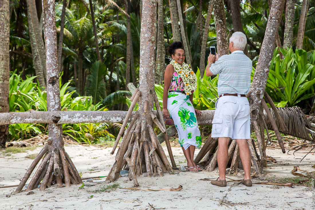Пара фотографируется в полинезийском лесу. Пляж около деревни Анапото, Риматара, архипелаг Острал (Тубуаи), Французская Полинезия. A beach near Anapoto village, Rimatara, the Austral archipelago (Tubuai), French Polynesia. Polynesian picnic, Polynesian dishes are laid on the table by Polynesian women. A couple is photographing in a Polynesian forest.