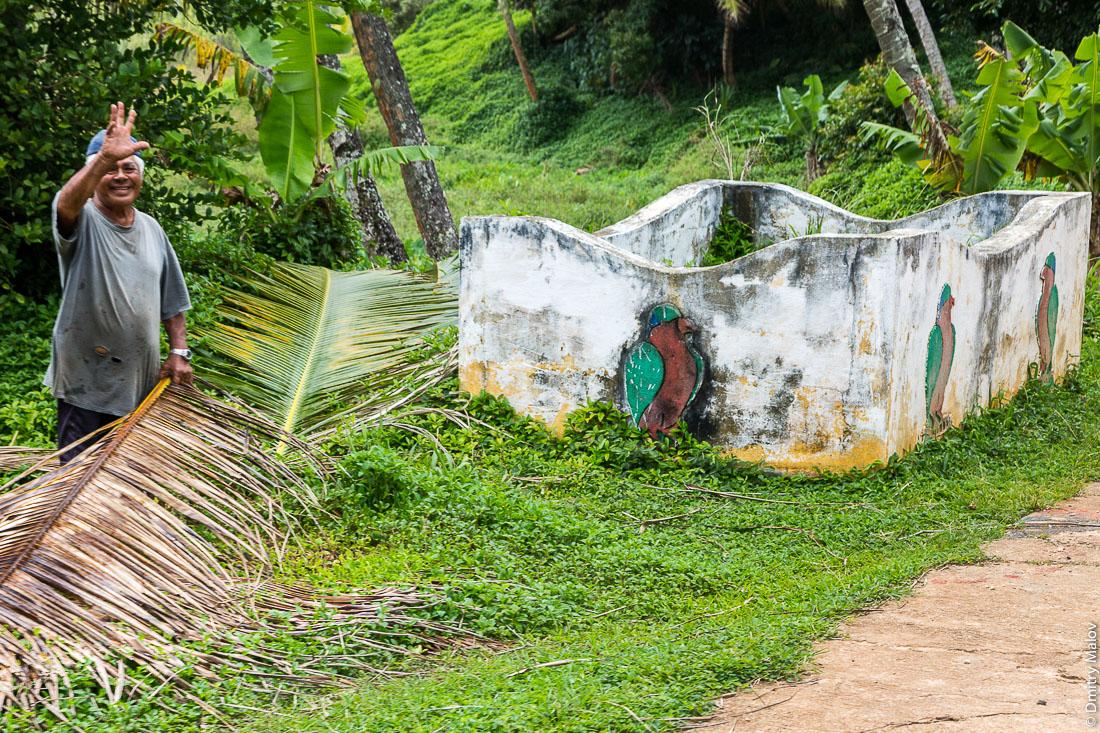 Мужчина, помойка и фреска с рубиновым лори-отшельником. Остров Риматара, архипелаг Острал (Тубуаи), Французская Полинезия. Rimatara, Austral archipelago (Tubuai), French Polynesia. A man and a ʻUra (Kuhl's lorikeet) mural