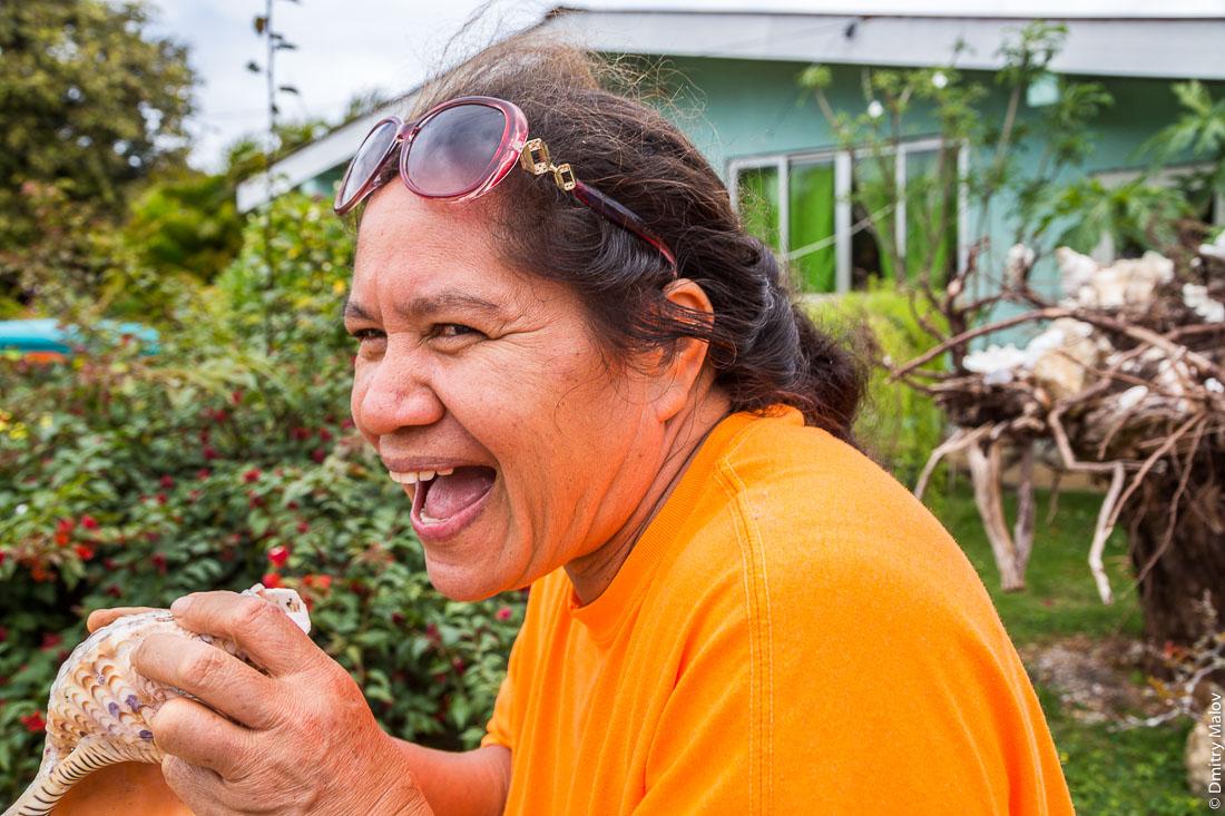 Женщина дует в полинезийский горн пу из раковины. Риматара, архипелаг Острал (Тубуаи), Французская Полинезия. Woman blowing a conch shell pū, Rimatara, the Austral archipelago (Tubuai), French Polynesia.