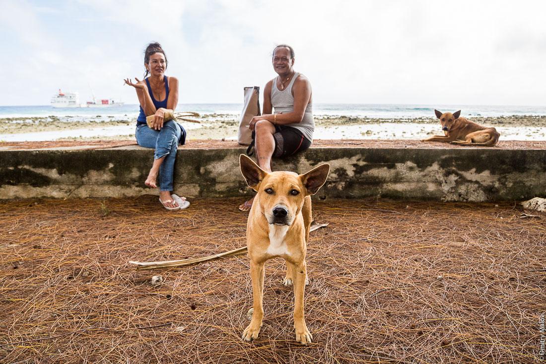 Полинезийцы и собаки на улицах Моэраи, остров Руруту, архипелаг Острал (Тубуаи), Французская Полинезия. Moerai, Rurutu, the Austral islands (Tubuai), French Polynesia. Local Polynesian people and dogs