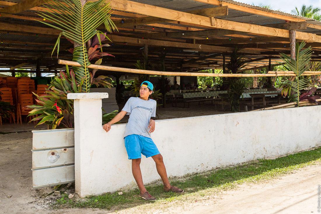 Мальчик подросток, забор. На улицах Аути (Хаути), остров Руруту, архипелаг Острал (Тубуаи), Французская Полинезия. Hauti village, Rurutu, the Austral islands (Tubuai), French Polynesia. A Polynesian teen boy standing on street at a fence.