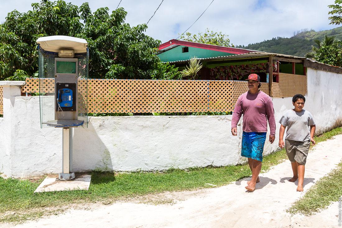 Мужчина, мальчик, телефонная будка, забор. На улицах Аути (Хаути), остров Руруту, архипелаг Острал (Тубуаи), Французская Полинезия. Hauti village, Rurutu, the Austral islands (Tubuai), French Polynesia. A man, a boy, a phone booth, a fence.