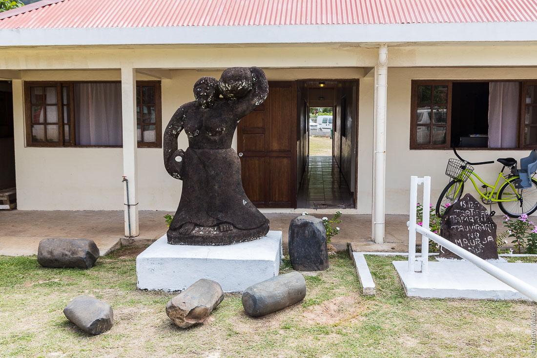 Статуя женщины перед мэрией Руруту, сделанная на Маркизских островах. Деревня Моэраи, остров Руруту, архипелаг Острал (Тубуаи), Французская Полинезия. Moerai, Rurutu, the Austral islands (Tubuai), French Polynesia. Marquesas-made Statue of woman at mairie of Rurutu