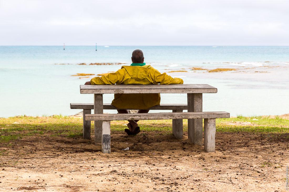 Полинезиец отдыхает на скамейке на берегу океана. Остров Тубуаи, архипелаг Острал, Французская Полинезия. Polynesian men rests on a bench by the ocean, Tubuai island, the Austral islands, French Polynesia.