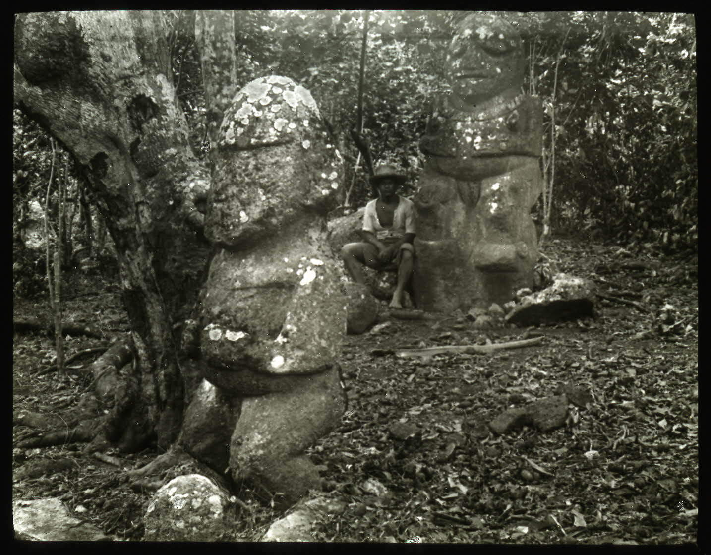 Photograph of two Tiʻi de Raivavae (Tiʻi Papa and Tiʻi One; or Heiata and Moana) and a Polynesian man. From archaeological expedition led by William Scoresby Routledge and Katherine Maria Routledge, 1921-1923, British Museum