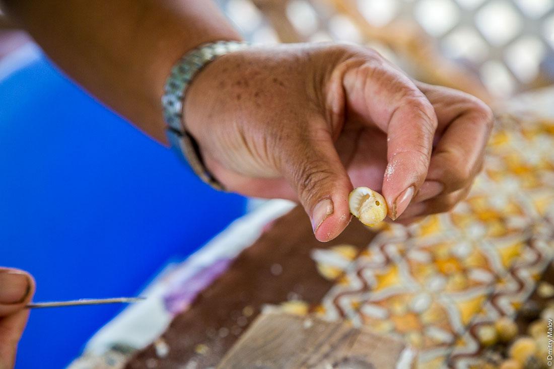 Полинезийка делает ожерелье из ракушек для провожания гостей. Остров Раиваваэ, архипелаг Острал (Тубуаи). Polynesian woman making a farewell seashell necklace. Raivavae island, Astral (Tubuai) Islands, French Polynesia.