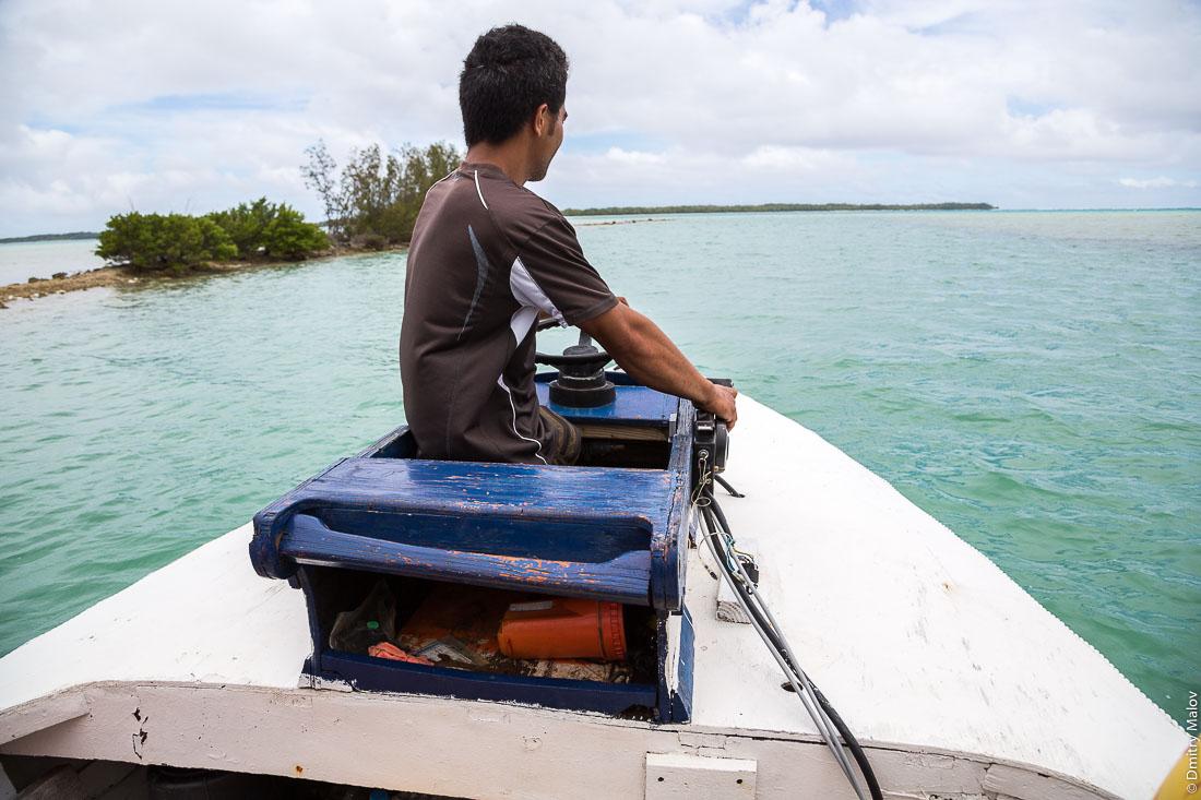 Полинезиец в лодке, остров Раиваваэ, архипелаг Острал (Тубуаи). Raivavae island, Astral (Tubuai) Islands, French Polynesia. A Polynesian man rides a fisherman boat.