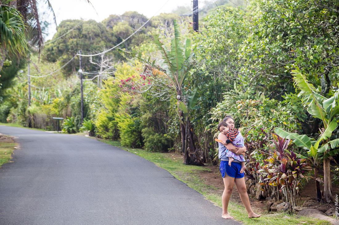 Дорога вокруг острова Раиваваэ, полинезийская девушка несёт ребёнка, архипелаг Острал (Тубуаи). The road around the island, Raivavae, Astral (Tubuai) Islands, French Polynesia. Polynesian girl carries a child