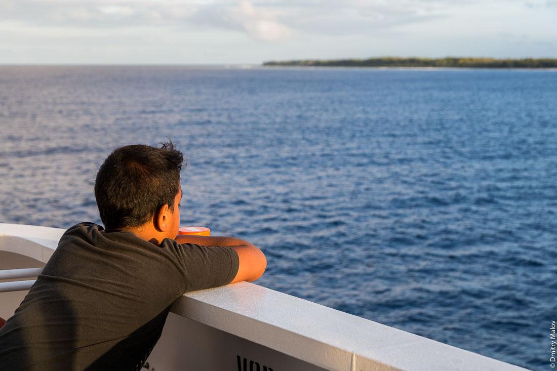 Корабль Tuhaa Pae IV отправляется из порта Раируа. Полинезийский мальчик-пассажир. Остров Раиваваэ, архипелаг Тубуаи (Острал), Французская Полинезия. Ship Tuhaa Pae IV is leaving the port of Rairua, Raivavae, Tubuai/Austral islands, French Polynesia. Polynesian boy, a passenger
