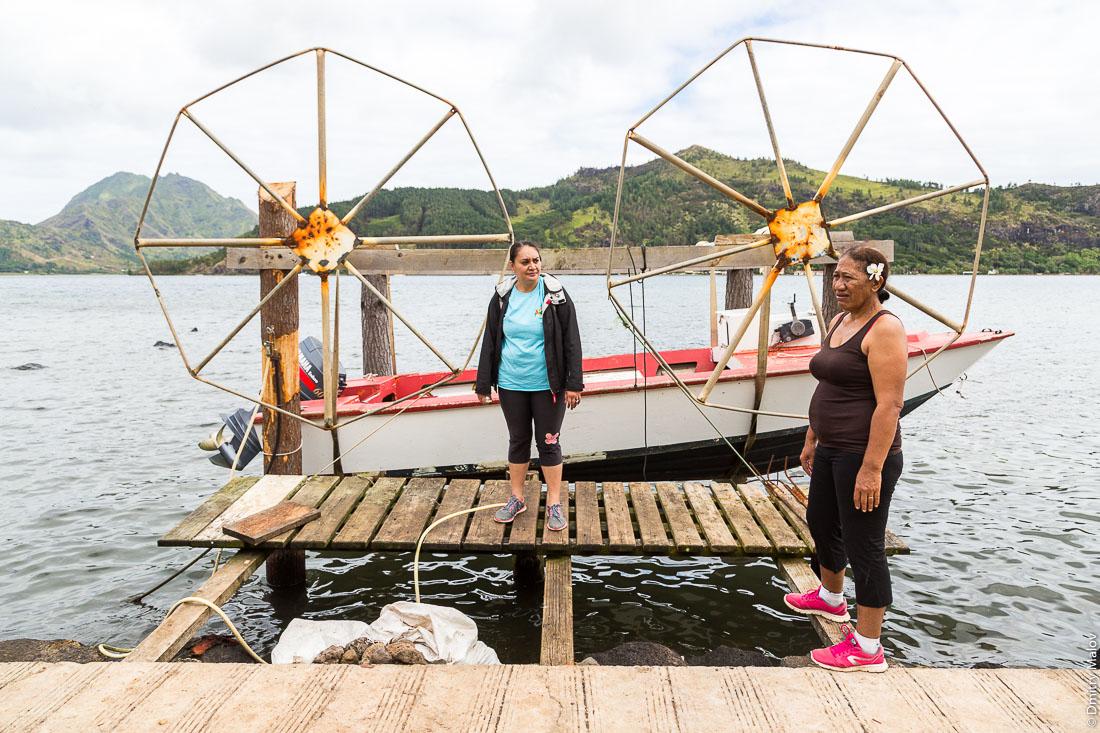 Хранение лодок на весу подвешенными на блоках. Две полинезийки. Остров Рапа-Ити, острова Басс, Французская Полинезия. Rapa-Iti, The Bass Islands, French Polynesia. Lifted Boat storage using pulleys. Two local Polynesian women.