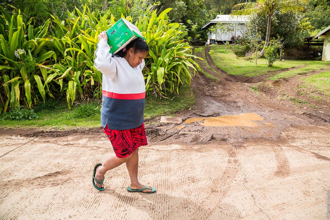 Полинезийская женщина несёт коробку. Остров Рапа-Ити, острова Басс, Французская Полинезия. Rapa-Iti, The Bass Islands, French Polynesia. A local Polynesian woman carries a box