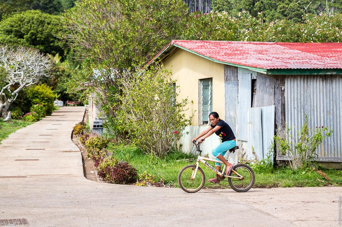 Местная полинезийская девочка на велосипеде. Ауреи, остров Рапа-Ити, архипелаг Басс, Французская Полинезия. Ahurei, Rapa-Iti, The Bass Islands, French Polynesia. A local Polynesian girl on a bicycle