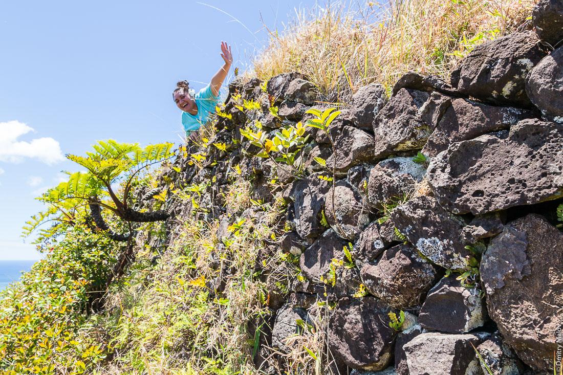 Каменная кладка на полинезийском форте Моронго Ута и местная полинезийская женщина, остров Рапа-Ити, острова Басс, Французская Полинезия. A Polynesian local woman and a stonework on Pare (Polynesian fort) of Morongo Uta, Rapa-Iti, The Bass Islands, French Polynesia.