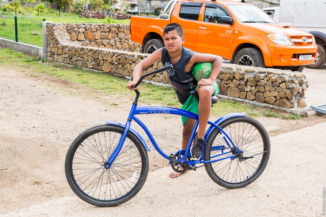 Местный полинезийский мальчик с футбольным мячом на велосипеде. Ауреи, остров Рапа-Ити, архипелаг Басс, Французская Полинезия. Ahurei, Rapa-Iti, The Bass Islands, French Polynesia. A local Polynesian boy on a bicycle with a football ball