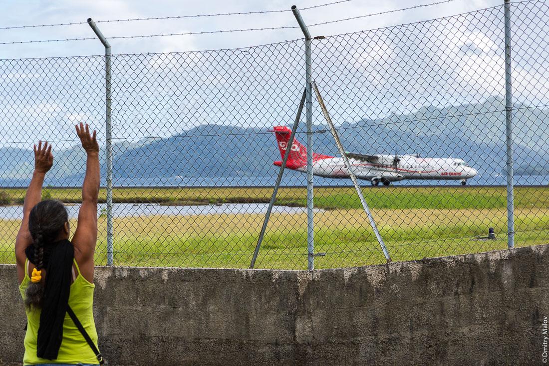 Полинезийска машет улетающему самолёту Раиатеа Air Tahiti ATR 72-600, Подветренные острова архипелага Общества, Французская Полинезия. Polynesian woman waves her hands to a leaving airplane at Raiatea airport, Leeward Islands, Society Islands, French Polynesia.