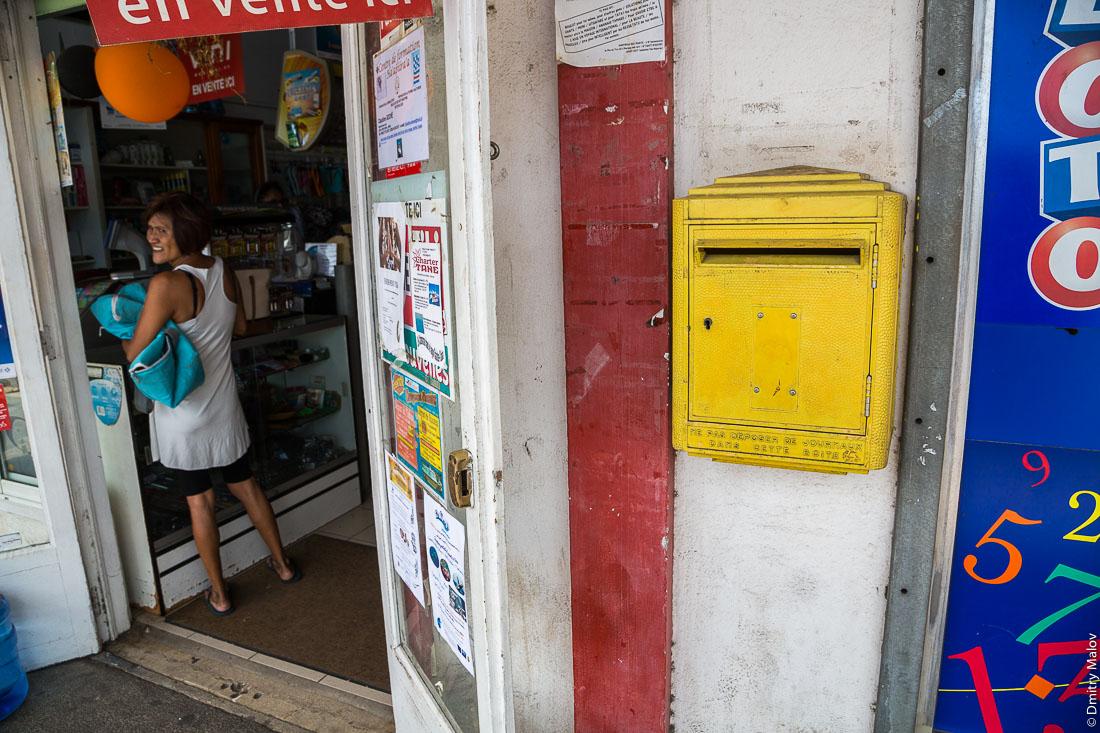 Ne pas déposer de journaux dans cette boîte. Магазин, покупательница, жёлтый почтовый ящик, лото. Город Утуроа, Раиатеа, Подветренные острова архипелага Общества, Французская Полинезия. Uturoa town, Raiatea, Leeward Islands,  Society Islands, French Polynesia. Shop, customer, woman, yellow mailbox, lotto.
