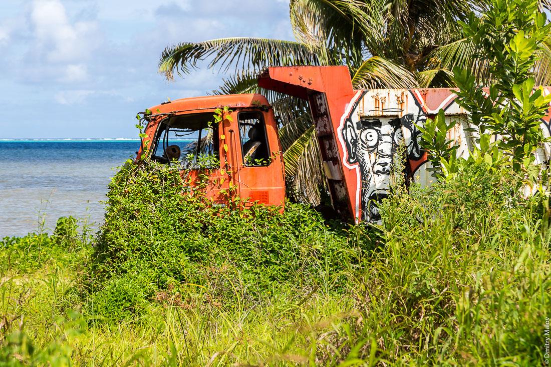 Грузовик зарастает в джунглях на берегу океана. A truck is overgrown in the jungle by the ocean coast. Раиатеа, Подветренные острова архипелага Общества, Французская Полинезия. Ra'iātea, Raiatea, Leeward Islands.
