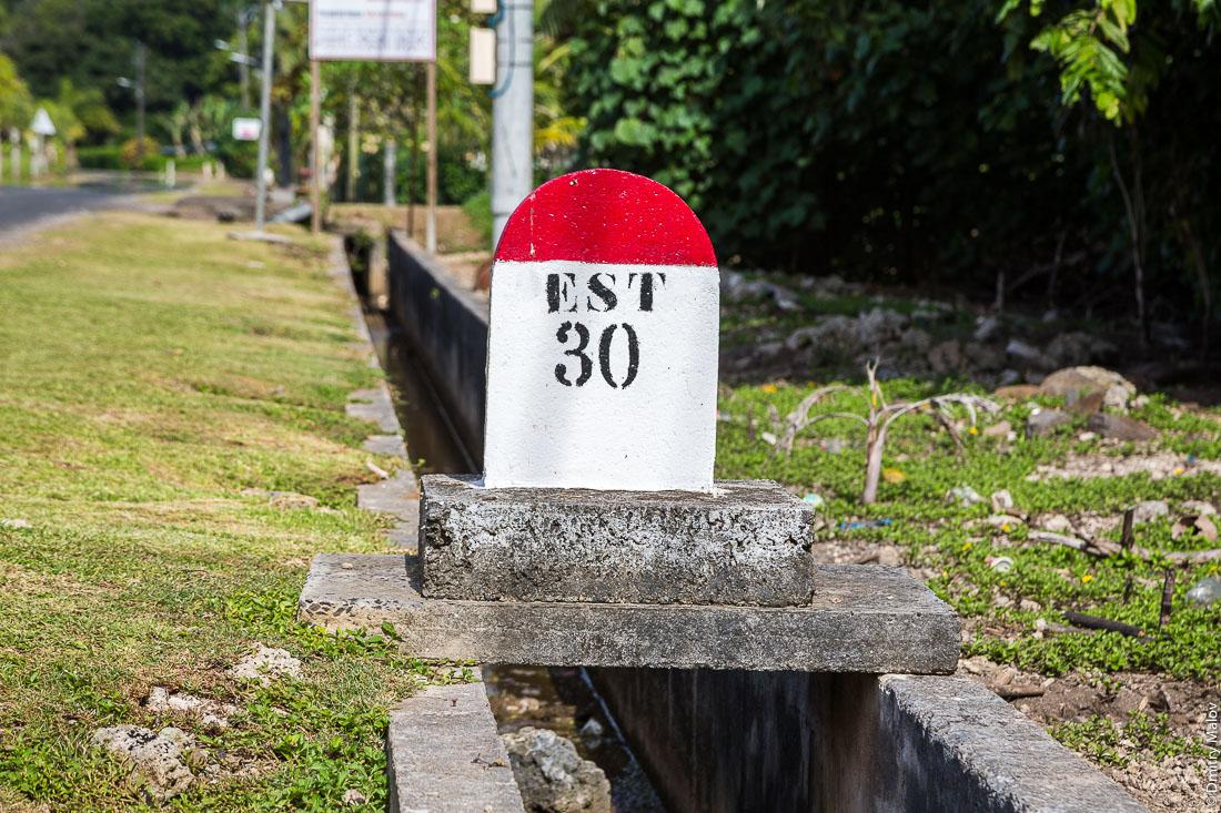 Километровый знак EST 30. Раиатеа, Подветренные острова архипелага Общества, Французская Полинезия. Raiatea, Society Islands, Leeward Islands, French Polynesia. A copra drying shed. PK, milestone, kilometer stone.