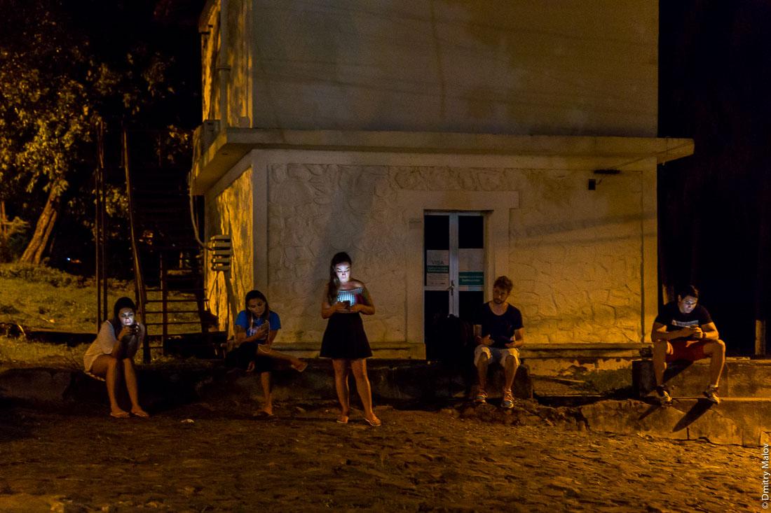 Молодёжь сидит в бесплатном интернете, остров Фернанду-ди-Норонья, Бразилия. Center of Vila dos Remédios, Island Fernando de Noronha, Brazil. Young people are using free Wi-Fi