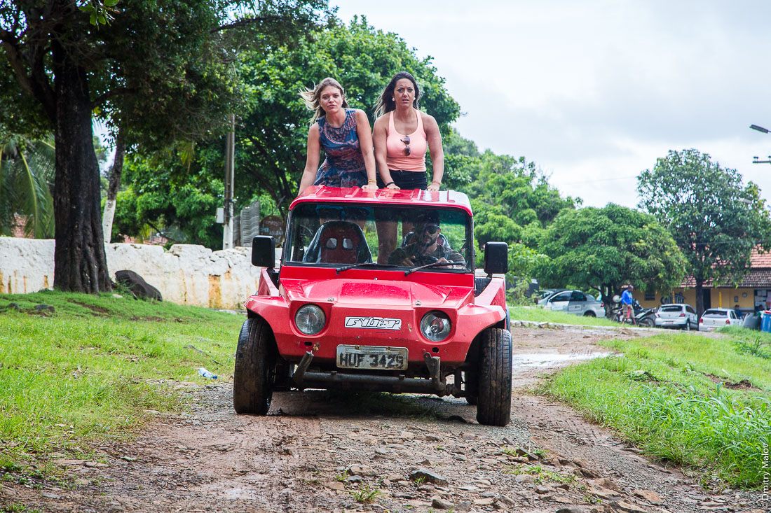Две девушки едут стоя в кузове багги стоя. Город Вила-дус-Ремедиус, остров Фернанду-ди-Норонья. Town centre of Vila dos Remédios, Island Fernando de Noronha, Brazil. Two girls are riding a buggy standing