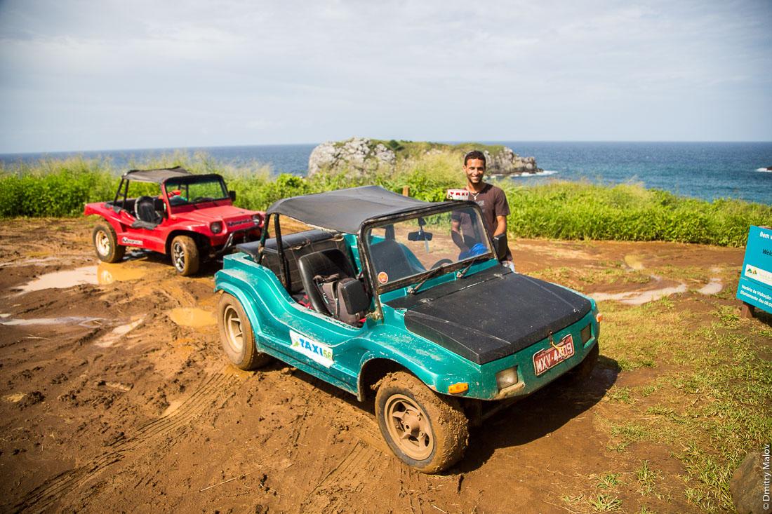 Мужчина и две машины-багги. Обрыв. Остров Фернанду-ди-Норонья. Town centre of Vila dos Remédios, Island Fernando de Noronha, Brazil. A man and two buggy cars