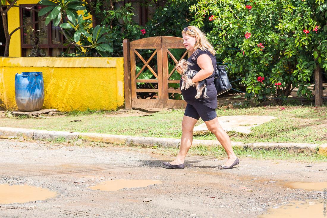 Толстая женщина несёт йоркширского терьера. Улица города Вила-дус-Ремедиус, остров Фернанду-ди-Норонья, Бразилия. Street of town of Vila dos Remédios, Island Fernando de Noronha, Brazil. A plus-size woman carries a Yorkshire terrier.