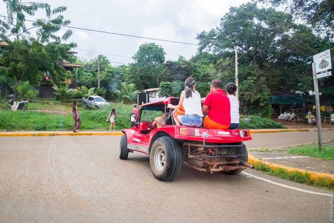 Трое едут в кузове багги. Город Вила-дус-Ремедиус, остров Фернанду-ди-Норонья. Town centre of Vila dos Remédios, Island Fernando de Noronha, Brazil. People are riding a buggy