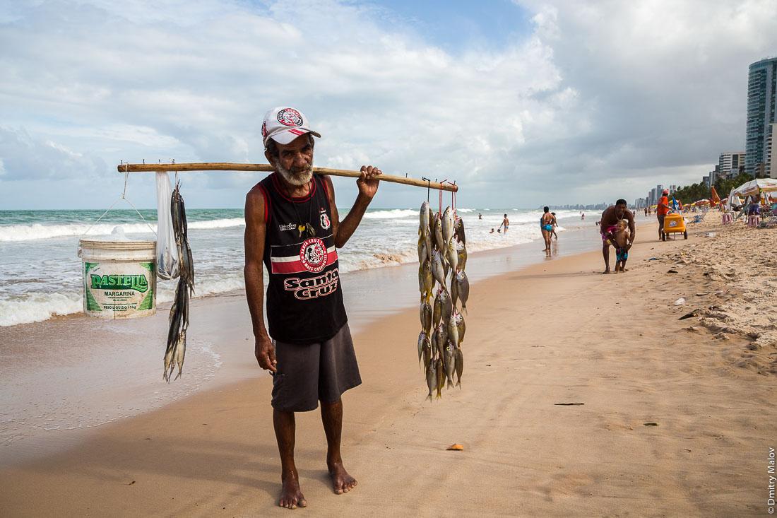 Ресифи, Пернамбуко, Бразилия. Вид городского пляжа Боа Виагем, мужчина с рыбой. Recife, state of Pernambuco, Brazil. A man with fish on Boa Viagem Beach