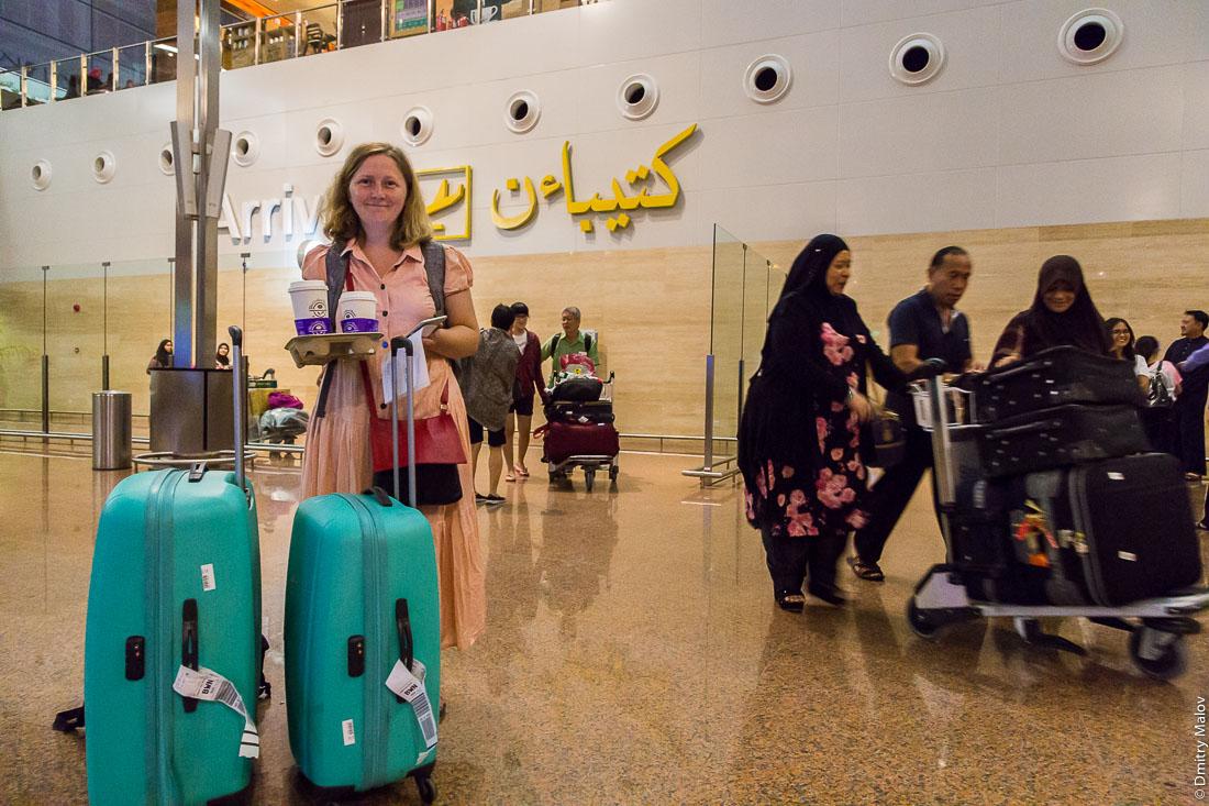 Внутри аэропорта султаната Бруней-Даруссалам. Inside Brunei airport arrivals (IATA: BWN, ICAO: WBSB). Muslim ladies with luggage wearing abaya. A western lady with coffee.