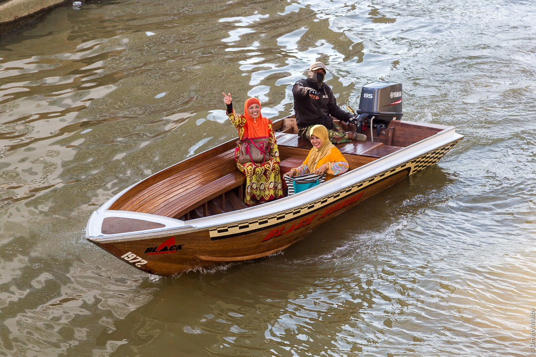 Три местных жителя (две девушки в мусульманских платках) в лодке, Бандар-Сери-Бегаван, Бруней-Даруссалам. Sungai Kianggeh. Three local residents (including two ladies in muslim outfit) in a taxi-boat, Bandar Seri Begawan, Brunei Darussalam.