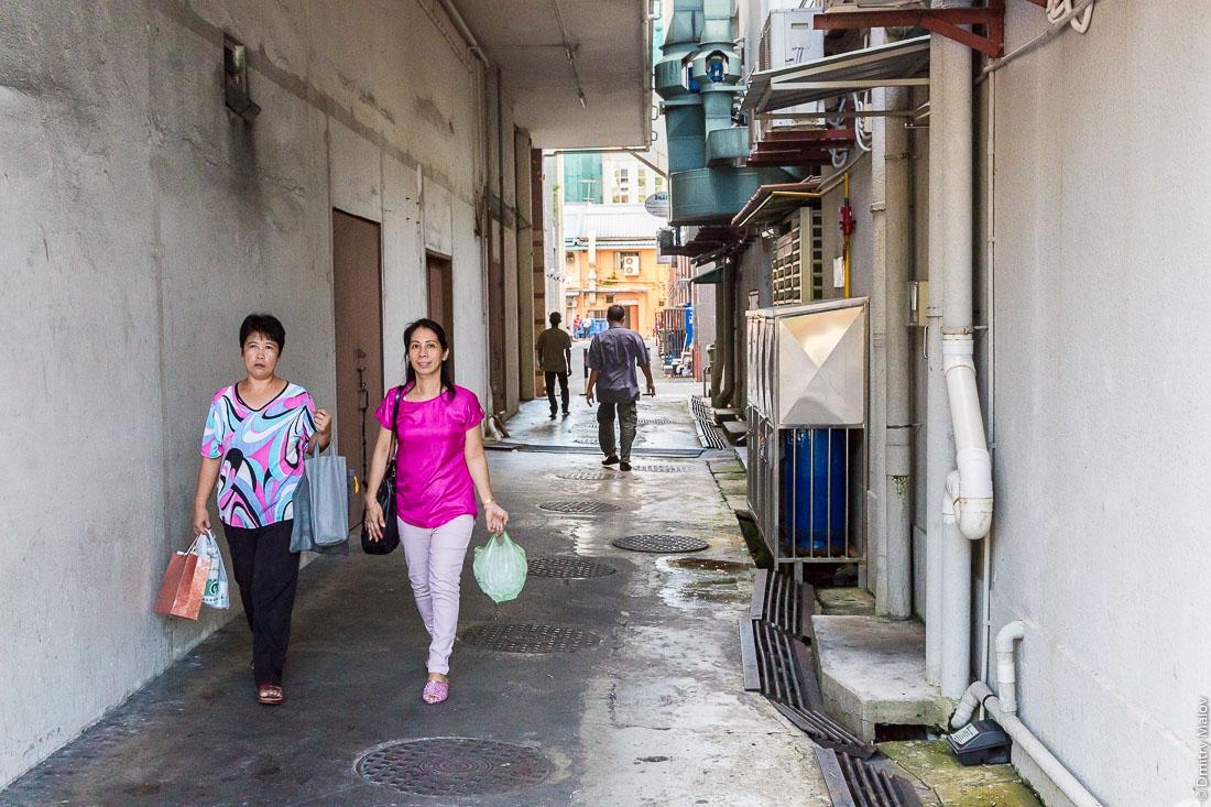 Люди - мужчины и женщины - в европейской одежде в переулке города Бандар-Сери-Бегаван, Бруней-Даруссалам. People - men and women - in European clothes in a side street of Bandar Seri Begawan, Negara Brunei Darussalam