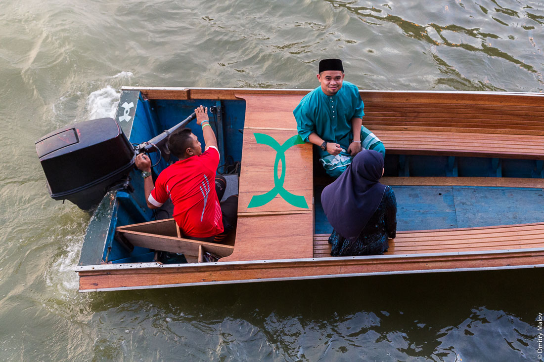 Три местных жителя (два мужчины, мужчина в национальной одежде, девушка в мусульманском платке) в лодке, река Бруней, Бандар-Сери-Бегаван, Бруней-Даруссалам. Brunei river. Three local residents (including a lady in muslim outfit) in a taxi-boat, Bandar Seri Begawan, Brunei Darussalam.