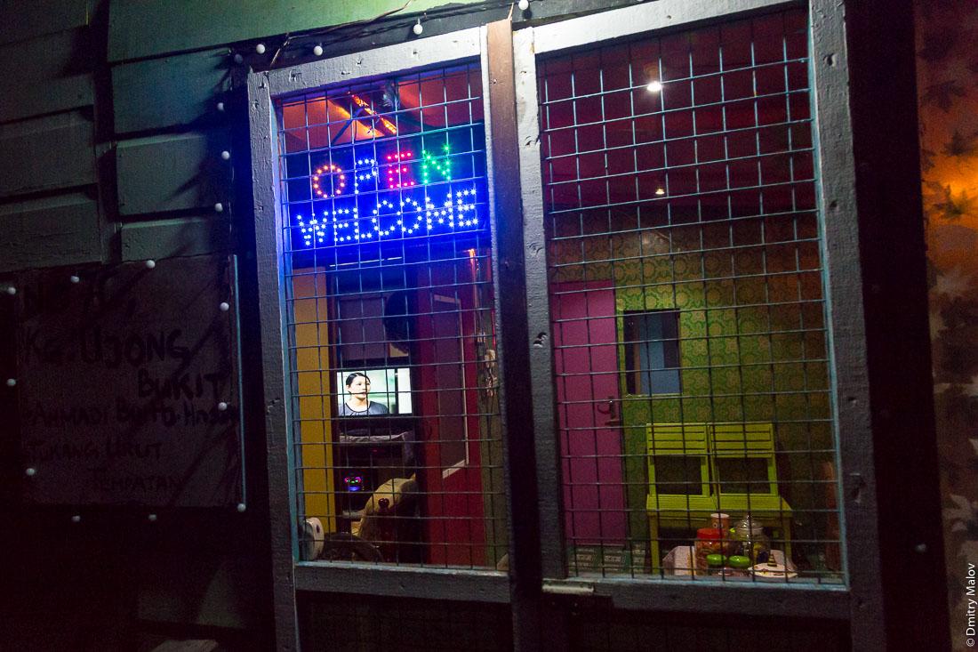 Open Welcome Light-emitting diodes sign. Район Тамой в деревне на сваях Кампунг-Айер ночью, Бандар-Сери-Бегаван, Бруней-Даруссалам. In Tamoi district, stilt village Kampong Ayer by night, Bandar Seri Begawan, Brunei Darussalam