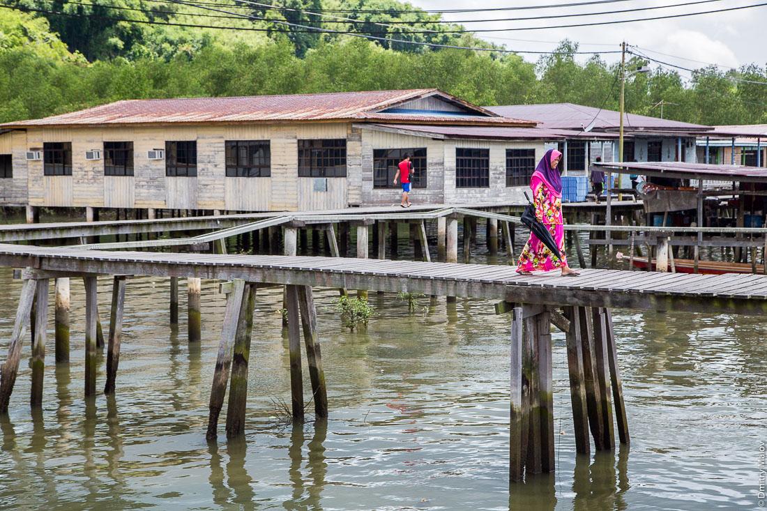 Женщина в мусульманских национальных одеждах. Деревня на сваях Кампунг-Айер, Бандар-Сери-Бегаван, Бруней-Даруссалам. A local woman in a muslim outfit. Kampong Ayer stilt village, Bandar Seri Begawan, Brunei Darussalam
