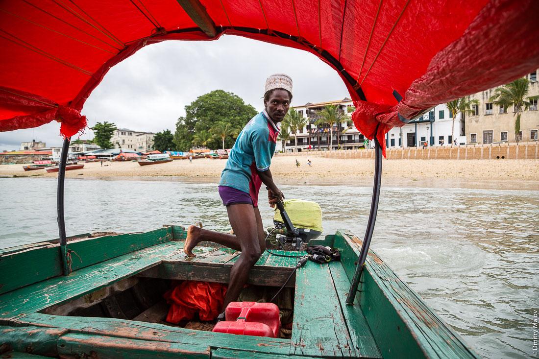 Дворцы на набережной Каменного города (Стоун-Таун), Занзибар-сити, остров Унгуджа, Танзания. Вид из лодки с чёрным местным мужчиной лодочник. Palaces on the embankment of Stone Town, Zanzibar City, Unguja island, Tanzania. As seen from a bot, a black boatman.
