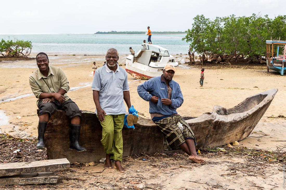 Три местных чёрных мужчины сидят на лодке-долблёнке на пляже. Остров Пемба, архипелаг Занзибар, Танзания. Three local black men are sitting on a dugout canoe on the beach. Pemba island, Zanzibar archipelago, Tanzania.