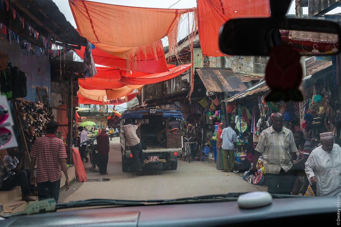 Рынок, базар, мужчина выпрыгивает из маршрутки дала-дала на ходу, город Чаки-Чаки, остров Пемба, Занзибар, Танзания. A man leaves running dala-dala on a market street, Bazaar at Chake-Chake town, Pemba island, Zanzibar, Tanzania.