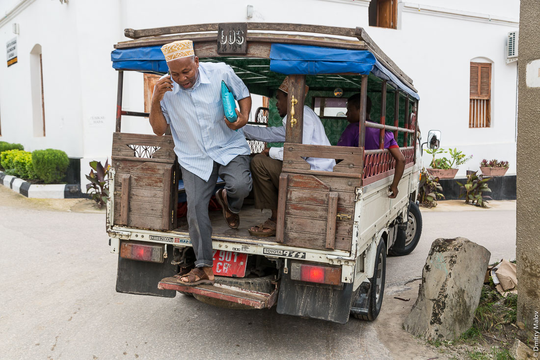 Мужчина выпрыгивает из маршрутки дала-дала на ходу и говорит по сотовому телефону, город Чаки-Чаки, остров Пемба, Занзибар, Танзания. A man leaves running dala-dala while talking on a mobile phone, Chake-Chake town, Pemba island, Zanzibar, Tanzania.
