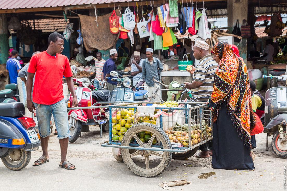 Рынок, чёрный мужчина с тележкой цитрусовых и женщина в мусульманской одежде, город Чаки-Чаки, остров Пемба, Занзибар, Танзания. Market, bazaar. A black man with a citrus truck and a woman in Muslim clothes, Chake-Chake town, Pemba island, Zanzibar, Tanzania.